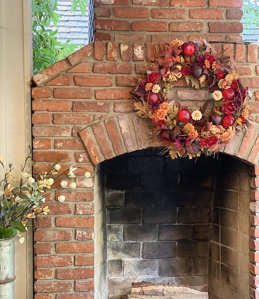 Fall wreath on back porch fireplace