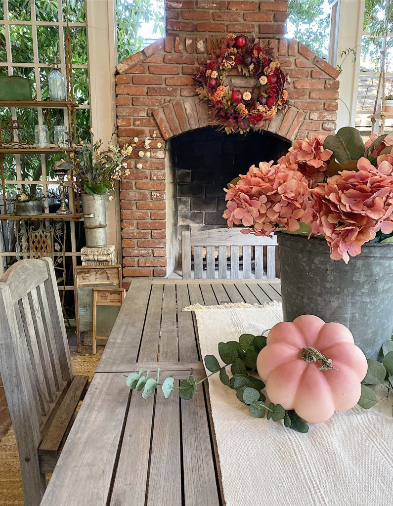 Back porch decorated with faux fall florals and pumpkins