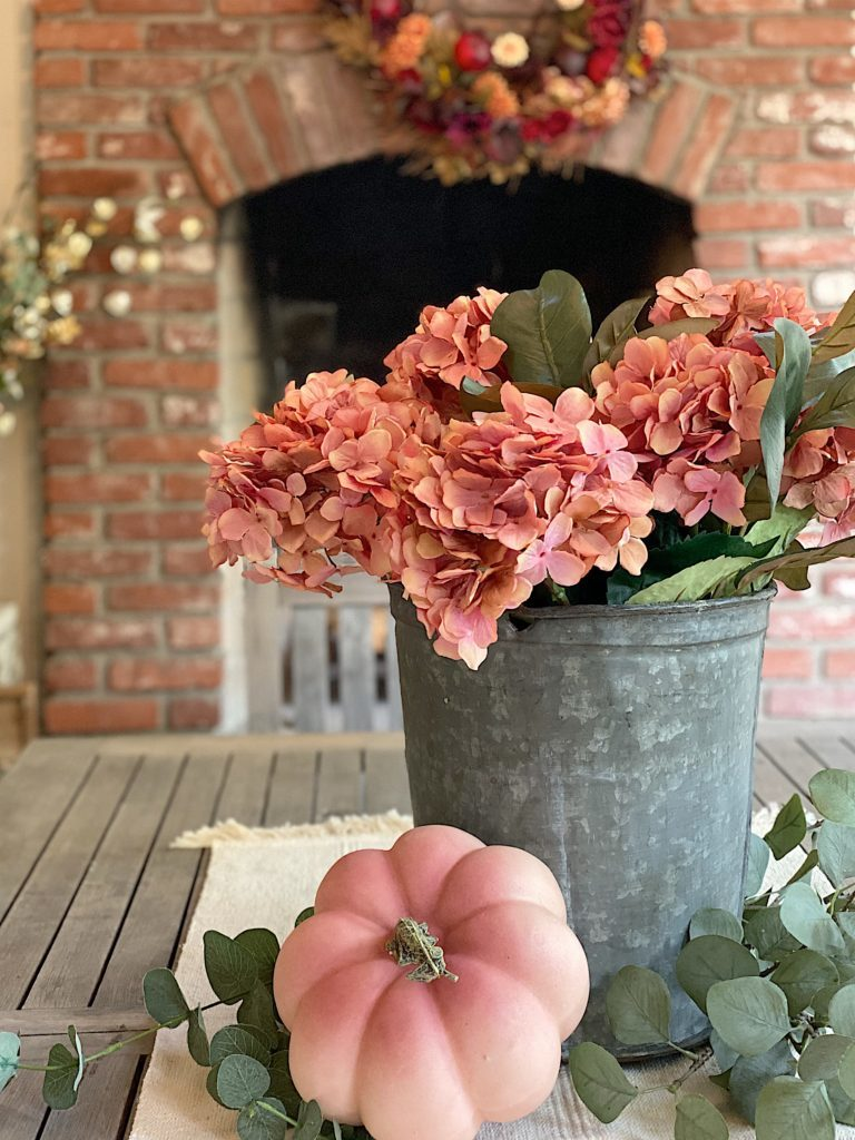 Blush fall hydrangeas in sap bucket on table
