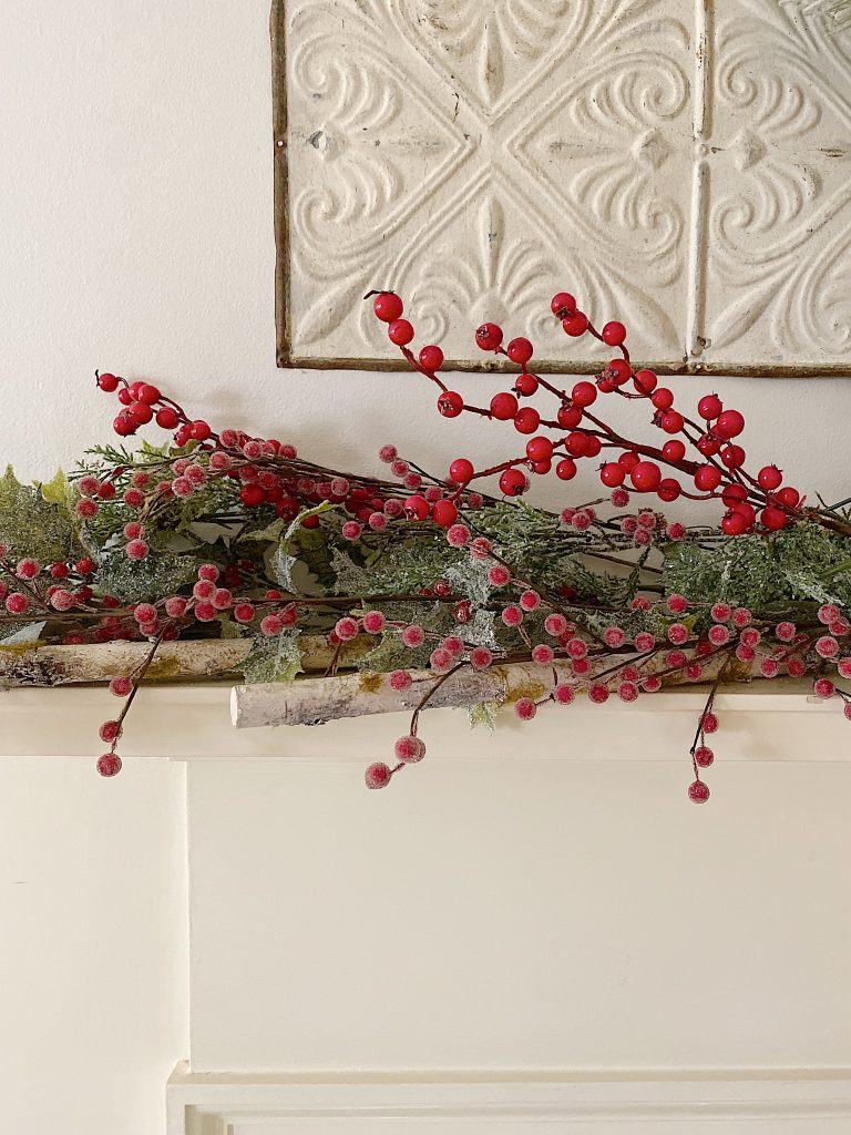 adding red berries to a mantel