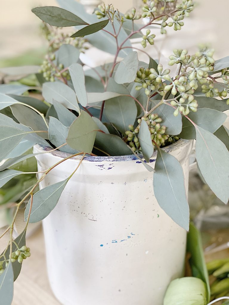 adding eucalyptus to floral arrangement